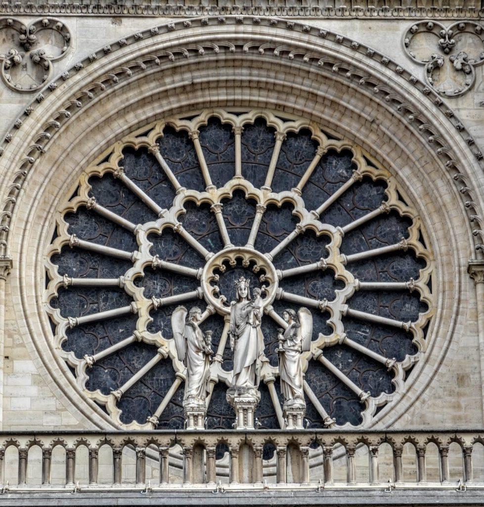 مجسمه حضرت مریم و حضرت عیسی در جلوی پنجره گل سرخی نمای غربی کلیسای نوتردام پاریس