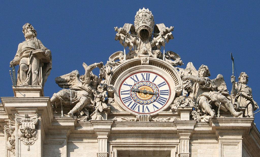 ساعت و مجسمه های تزئینی و تاج پاپ در نمای غربی کلیسای سن پیتر
